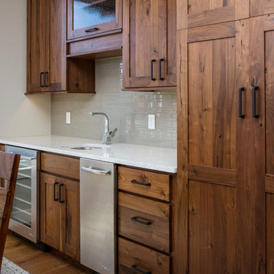 Large elegant l-shaped light wood floor open concept kitchen photo in Other with an undermount sink, shaker cabinets, dark wood cabinets, quartz countertops, gray backsplash, glass tile backsplash, stainless steel appliances and an island