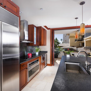 Photo of a mid-sized tropical separate kitchen in Hawaii with an undermount sink, shaker cabinets, limestone benchtops, slate splashback, stainless steel appliances, porcelain floors, with island, beige floor and grey benchtop.