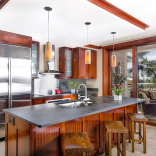 Design ideas for a mid-sized tropical separate kitchen in Hawaii with slate splashback, stainless steel appliances, porcelain floors, with island, beige floor and grey benchtop.
