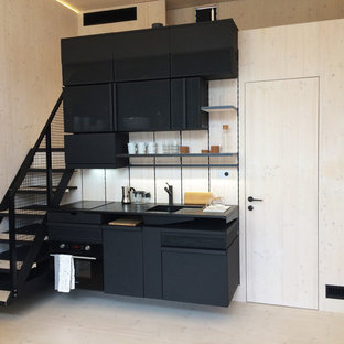 Photo of a small scandinavian single-wall kitchen in Essex with flat-panel cabinets, black cabinets, black appliances and light hardwood flooring.