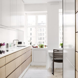 This is an example of a small modern single-wall eat-in kitchen in Other with flat-panel cabinets, light wood cabinets, a single-bowl sink, recycled glass benchtops, white splashback, glass sheet splashback, white appliances, painted wood floors and with island.