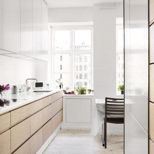 Foto di una piccola cucina minimalista con ante lisce, ante in legno chiaro, lavello a vasca singola, top in vetro riciclato, paraspruzzi bianco, paraspruzzi con lastra di vetro, elettrodomestici bianchi, pavimento in legno verniciato e isola
