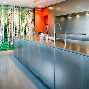 エスビャールのインダストリアルスタイルのおしゃれなキッチン (フラットパネル扉のキャビネット、黒いキャビネット、リノリウムの床、グレーの床) の写真