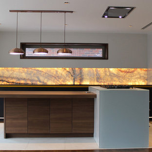 Mid-sized modern open concept kitchen pictures - Mid-sized minimalist l-shaped medium tone wood floor open concept kitchen photo in London with a double-bowl sink, flat-panel cabinets, glass countertops, red backsplash, black appliances and an island
