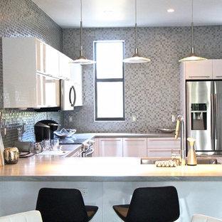 マイアミの中サイズのコンテンポラリースタイルのおしゃれなキッチン (アンダーカウンターシンク、フラットパネル扉のキャビネット、白いキャビネット、コンクリートカウンター、茶色いキッチンパネル、モザイクタイルのキッチンパネル、シルバーの調理設備の、コンクリートの床、ベージュの床、ベージュのキッチンカウンター) の写真