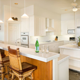 Large coastal eat-in kitchen pictures - Large beach style u-shaped limestone floor eat-in kitchen photo in Hawaii with recessed-panel cabinets, white cabinets, tile countertops, white backsplash, ceramic backsplash, white appliances and an island