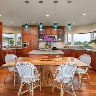 Idee per una grande cucina tropicale con ante lisce, isola, pavimento marrone, lavello da incasso, ante in legno bruno, top in granito, paraspruzzi bianco, paraspruzzi con piastrelle di vetro, elettrodomestici in acciaio inossidabile e parquet scuro