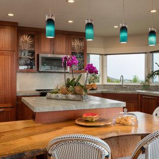Große Kolonialstil Wohnküche in U-Form mit Einbauwaschbecken, flächenbündigen Schrankfronten, dunklen Holzschränken, Granit-Arbeitsplatte, Küchenrückwand in Weiß, Rückwand aus Glasfliesen, Küchengeräten aus Edelstahl, dunklem Holzboden, Kücheninsel und braunem Boden in Hawaii
