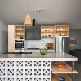 Photo of a contemporary galley open plan kitchen in Adelaide with a double-bowl sink, open cabinets, light wood cabinets, grey splashback, mosaic tile splashback, stainless steel appliances, concrete floors, with island and grey floor.