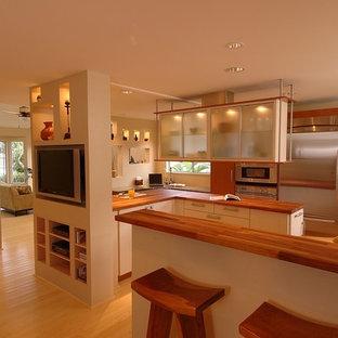 Imagen de cocina asiática, abierta, con armarios tipo vitrina, electrodomésticos de acero inoxidable y encimera de madera