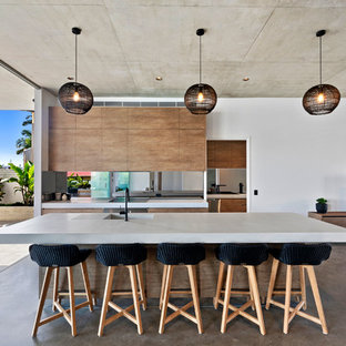Contemporary galley open plan kitchen in Sunshine Coast with an integrated sink, flat-panel cabinets, medium wood cabinets, window splashback, stainless steel appliances, concrete floors, with island, brown floor and white benchtop.