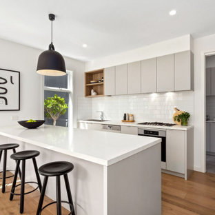 Design ideas for a contemporary galley kitchen in Melbourne with flat-panel cabinets, grey cabinets, white splashback, subway tile splashback, stainless steel appliances, medium hardwood floors, a peninsula, brown floor and white benchtop.