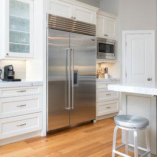 Идея дизайна: угловая кухня-гостиная среднего размера в стиле современная классика с фасадами в стиле шейкер, белыми фасадами, техникой из нержавеющей стали, светлым паркетным полом, врезной раковиной, столешницей из кварцевого агломерата, серым фартуком, фартуком из плитки кабанчик, островом и коричневым полом
