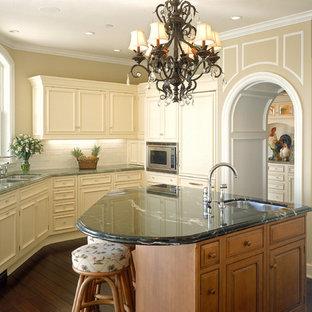 Immagine di una grande cucina ad U chiusa con lavello a doppia vasca, ante con riquadro incassato, ante beige, paraspruzzi bianco, paraspruzzi con piastrelle diamantate, elettrodomestici da incasso, top in marmo, parquet scuro e isola