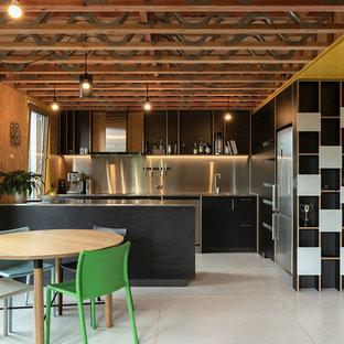 Modelo de cocina comedor en L, contemporánea, con armarios con paneles lisos, puertas de armario negras, encimera de acero inoxidable, salpicadero verde, salpicadero de metal, electrodomésticos de acero inoxidable, península, suelo blanco, encimeras grises y fregadero integrado
