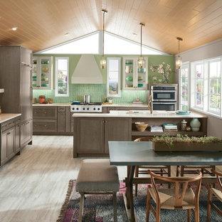 他の地域のトランジショナルスタイルのおしゃれなキッチン (落し込みパネル扉のキャビネット、中間色木目調キャビネット、緑のキッチンパネル、シルバーの調理設備、グレーの床) の写真