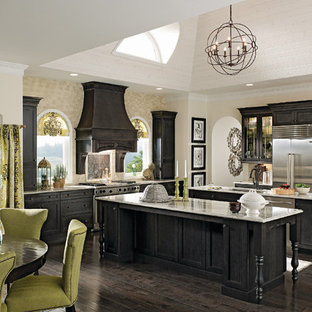 Photo of a large transitional l-shaped eat-in kitchen in Richmond with an undermount sink, shaker cabinets, black cabinets, granite benchtops, beige splashback, stainless steel appliances, dark hardwood floors, multiple islands and brown floor.