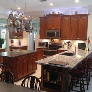 Klassische Küche in L-Form mit Waschbecken, profilierten Schrankfronten, braunen Schränken, Marmor-Arbeitsplatte, Küchenrückwand in Weiß, Kücheninsel, weißem Boden und bunter Arbeitsplatte in Tampa