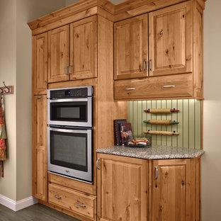 Ejemplo de cocina en U, rústica, de tamaño medio, abierta, con armarios con paneles con relieve, puertas de armario de madera oscura, salpicadero gris, electrodomésticos de acero inoxidable, suelo de madera en tonos medios y una isla