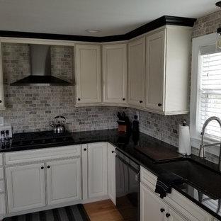 Wohnküche mit profilierten Schrankfronten, weißen Schränken, Granit-Arbeitsplatte, bunter Rückwand, Küchengeräten aus Edelstahl, braunem Holzboden, Kücheninsel und rosa Arbeitsplatte in Boston