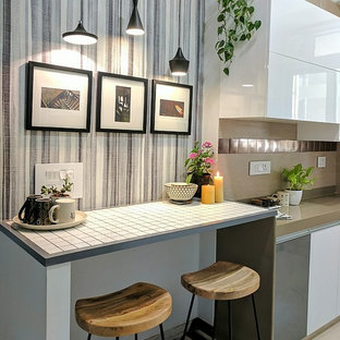 Photo of a scandinavian kitchen in Mumbai with flat-panel cabinets, white cabinets, metallic splashback, metal splashback and beige benchtop.