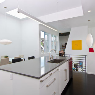 Minimalist eat-in kitchen photo in Seattle with an undermount sink, flat-panel cabinets, white cabinets and stainless steel appliances