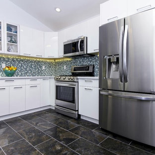 Large contemporary u-shaped separate kitchen in San Francisco with an undermount sink, flat-panel cabinets, white cabinets, limestone benchtops, multi-coloured splashback, mosaic tile splashback, stainless steel appliances, slate floors, no island, black floor and white benchtop.