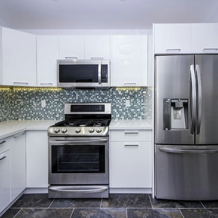 Design ideas for a large contemporary u-shaped separate kitchen in San Francisco with an undermount sink, flat-panel cabinets, white cabinets, stainless steel appliances, no island, white benchtop, limestone benchtops, multi-coloured splashback, mosaic tile splashback, slate floors and black floor.