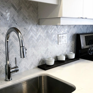 トロントの中サイズのコンテンポラリースタイルのおしゃれなキッチン (アンダーカウンターシンク、フラットパネル扉のキャビネット、濃色木目調キャビネット、木材カウンター、白いキッチンパネル、大理石のキッチンパネル、シルバーの調理設備、無垢フローリング、茶色い床、白いキッチンカウンター) の写真