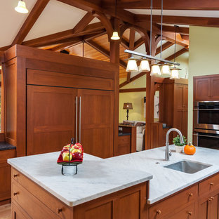 Arts and crafts l-shaped open plan kitchen in DC Metro with an undermount sink, shaker cabinets, medium wood cabinets, marble benchtops, black splashback, stainless steel appliances, light hardwood floors and with island.