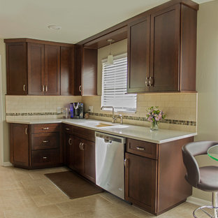 This is an example of a small transitional galley separate kitchen in Detroit with an integrated sink, recessed-panel cabinets, dark wood cabinets, quartzite benchtops, beige splashback, subway tile splashback, stainless steel appliances and porcelain floors.