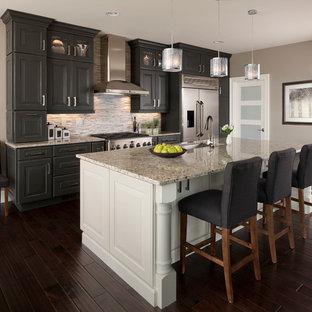 Exemple d'une grande cuisine parallèle chic avec un évier encastré, un placard avec porte à panneau surélevé, des portes de placard grises, une crédence en carreau briquette, un électroménager en acier inoxydable, une crédence beige, un sol en bois foncé, un îlot central et un plan de travail en quartz modifié.