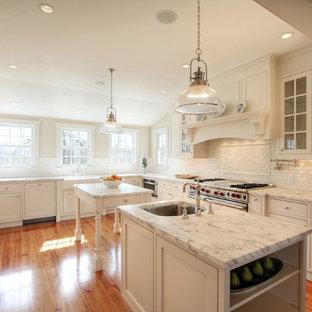 フィラデルフィアの広いビーチスタイルのおしゃれなキッチン (ドロップインシンク、フラットパネル扉のキャビネット、白いキャビネット、大理石カウンター、白いキッチンパネル、セラミックタイルのキッチンパネル、シルバーの調理設備、無垢フローリング) の写真