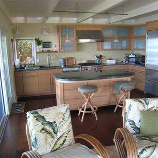 ハワイの中サイズのトロピカルスタイルのおしゃれなキッチン (アンダーカウンターシンク、フラットパネル扉のキャビネット、淡色木目調キャビネット、御影石カウンター、モザイクタイルのキッチンパネル、シルバーの調理設備の、コンクリートの床、赤い床、黄色いキッチンパネル) の写真