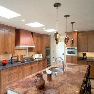 オレンジカウンティの大きいサンタフェスタイルのおしゃれなキッチン (シェーカースタイル扉のキャビネット、中間色木目調キャビネット、ダブルシンク、ベージュキッチンパネル、セラミックタイルのキッチンパネル、シルバーの調理設備の、セラミックタイルの床) の写真