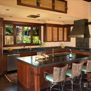This is an example of a mid-sized tropical l-shaped open plan kitchen in Hawaii with an integrated sink, recessed-panel cabinets, medium wood cabinets, granite benchtops, black splashback, stone slab splashback, stainless steel appliances, concrete floors and with island.