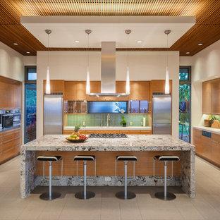 ハワイの中サイズのトロピカルスタイルのおしゃれなキッチン (フラットパネル扉のキャビネット、中間色木目調キャビネット、緑のキッチンパネル、ガラスタイルのキッチンパネル、アンダーカウンターシンク、御影石カウンター、シルバーの調理設備の、磁器タイルの床、ベージュの床) の写真