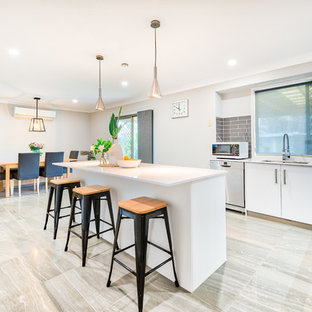 This is an example of a contemporary l-shaped eat-in kitchen in Brisbane with an undermount sink, flat-panel cabinets, white cabinets, grey splashback, window splashback, stainless steel appliances, with island and grey floor.