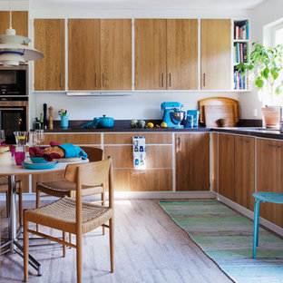 Photo of a midcentury l-shaped eat-in kitchen in Gothenburg with flat-panel cabinets, medium wood cabinets, stainless steel appliances, no island and granite benchtops.