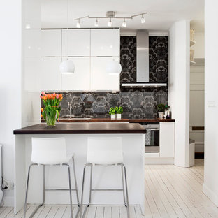 Inspiration for a mid-sized scandinavian single-wall eat-in kitchen in Stockholm with an undermount sink, flat-panel cabinets, white cabinets, black splashback, stainless steel appliances, painted wood floors, wood benchtops and with island.