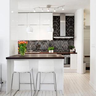 Immagine di una cucina scandinava di medie dimensioni con lavello sottopiano, ante lisce, ante bianche, paraspruzzi nero, elettrodomestici in acciaio inossidabile, pavimento in legno verniciato, top in legno e isola
