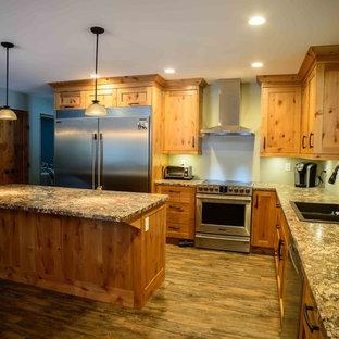 バンクーバーの小さいラスティックスタイルのおしゃれなキッチン (ドロップインシンク、シェーカースタイル扉のキャビネット、淡色木目調キャビネット、ラミネートカウンター、シルバーの調理設備、クッションフロア) の写真