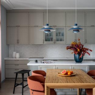 На фото: прямая кухня среднего размера в скандинавском стиле с обеденным столом, белым полом, фасадами с утопленной филенкой, серыми фасадами, белым фартуком, островом и белой столешницей с