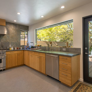 Photo of a mid-sized contemporary l-shaped open plan kitchen in San Francisco with an undermount sink, flat-panel cabinets, medium wood cabinets, grey splashback, slate splashback, stainless steel appliances, no island and grey floor.