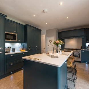 This is an example of a medium sized classic l-shaped open plan kitchen in London with a belfast sink, shaker cabinets, blue cabinets, quartz worktops, white splashback, stainless steel appliances, an island and white worktops.