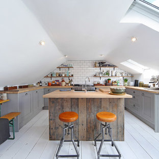 Small industrial u-shaped eat-in kitchen in London with a farmhouse sink, grey cabinets, wood benchtops, stainless steel appliances, painted wood floors, with island, raised-panel cabinets, white splashback and subway tile splashback.