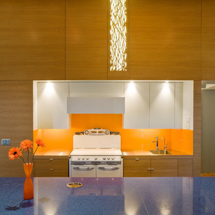 Contemporary galley kitchen in Omaha with an integrated sink, orange splashback, white appliances and blue benchtop.