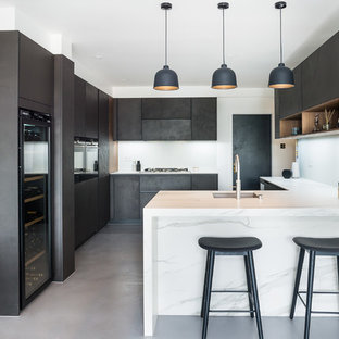 This is an example of a medium sized contemporary u-shaped kitchen in London with a submerged sink, flat-panel cabinets, black cabinets, concrete flooring, a breakfast bar, grey floors and white worktops.