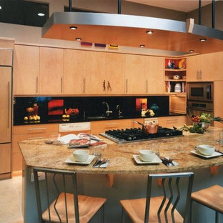 Inspiration for a mid-sized contemporary single-wall ceramic floor and beige floor eat-in kitchen remodel in Albuquerque with an undermount sink, flat-panel cabinets, light wood cabinets, marble countertops, black backsplash, stone slab backsplash, stainless steel appliances and an island