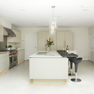 This is an example of a large contemporary enclosed kitchen in Hertfordshire with a double-bowl sink, flat-panel cabinets, quartz worktops, stainless steel appliances, ceramic flooring, an island, white floors, white worktops, beige cabinets and metallic splashback.